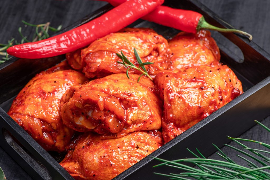 Chicken with marinade and chillies in dish