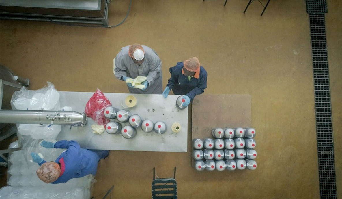 View of workers labelling sauce bottles