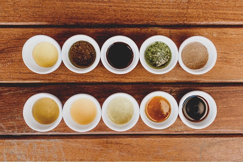 Various sauces in small bowls on wooden table