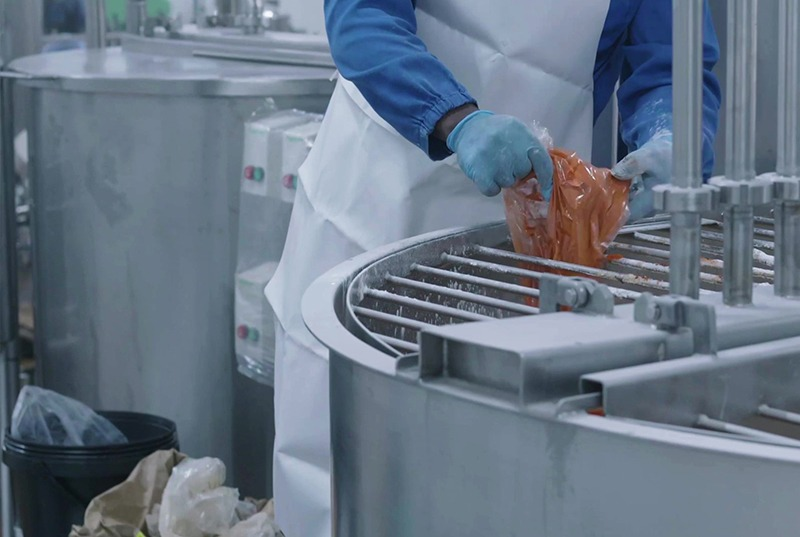 filling up a cooking pot in a sauce manufacturing factory