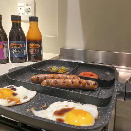 Pan with eggs and sausages. Sauces in background