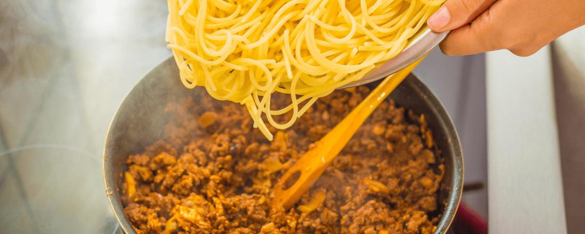 Pouring Spaghetti into pot of bolognaise