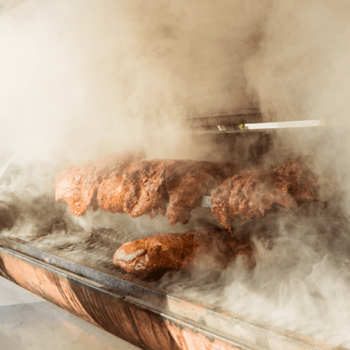 Smoke coming out of a smoker while cooking meat