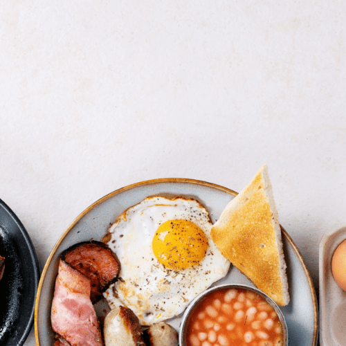 full breakfast being served on plates with sausages, eggs, tomatoes and baked beans